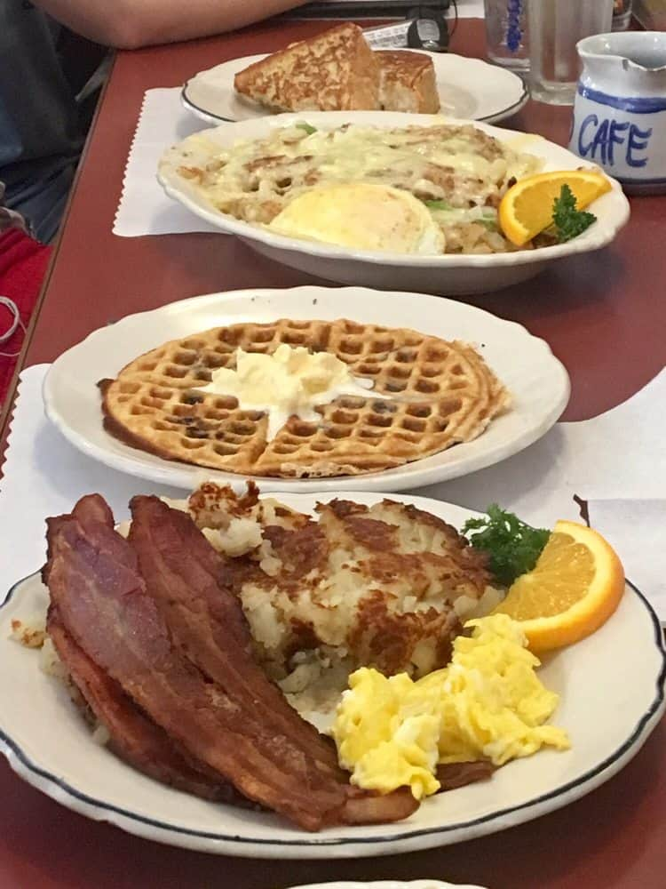 Breakfast has been served with thick slices of toast, cheese-covered German potatoes, a plate of waffles with a scoop of butter melting in the middle of them, and a plate of hashbrowns, bacon and scrambled eggs.