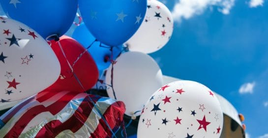 Photo of red, white and blue balloons with stars, and a red and white stripey ballon against a blue sky by Tom Dahm